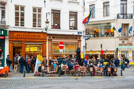 frites: BRUSSELS, BELGIUM - MARCH 15: People enjoying traditional belgium fries at one of many belgian frites restaurants in Brussels, March 15, 2015