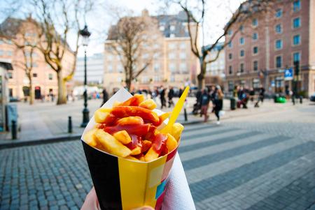 ブリュッセルの街の手で trypical のベルギーのフライド ポテトを持ってください。