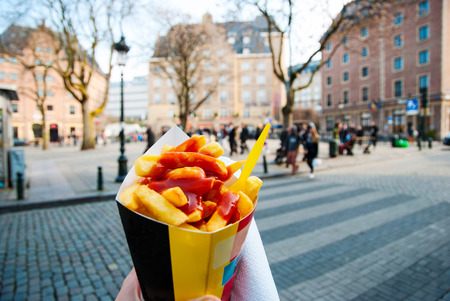 Holding trypical belgian fries in hand in the streets of Brussels
