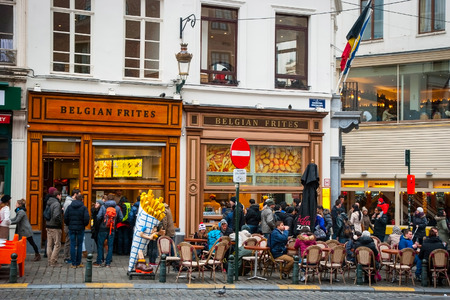 BRUSSELS, BELGIUM - MARCH 15: People enjoying traditional belgium fries at one of many belgian frites restaurants in Brussels, March 15, 2015