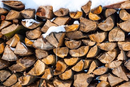 lumbering: Stacked wood timber covered with snow Stock Photo