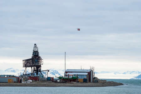 polar station: Helicopter flying over the port in Longyearbyen, Svalbard, Norway