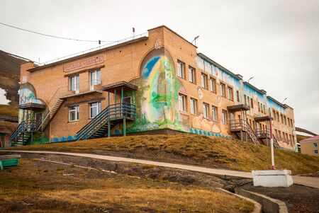 communists: BARENTSBURG, NORWAY - JUNE 21: Colorful painitings with norwegian and russian motifs pained on school facade on Barentsburg school on June 21, 2015