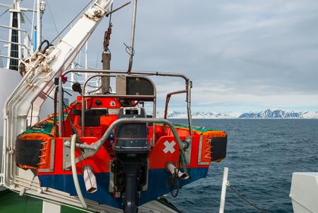 bateau: Bateau de sauvetage attaché sur le navire principal donnant sur l'océan