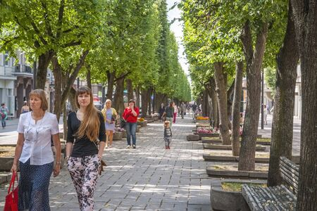 kaunas: KAUNAS, LITHUANIA - JULY 16: People walking in the promenade under the shadow of threes in Kaunas downtown on July 16, 2015 Editorial