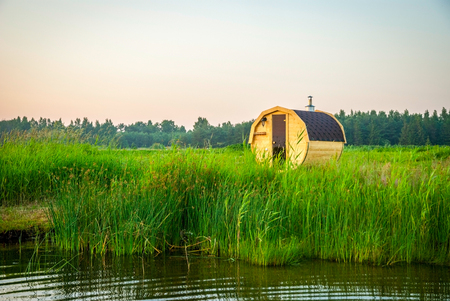 Wooden outdoor sauna by the lake in summer sunset Stock Photo