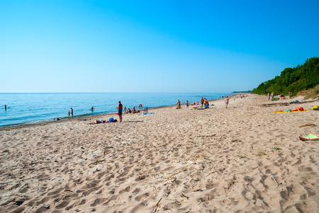 4 people: KLAIPEDA, LITHUANIA - JULY 4: People on sandy beach in Klaipeda under sunlight. July 2016.