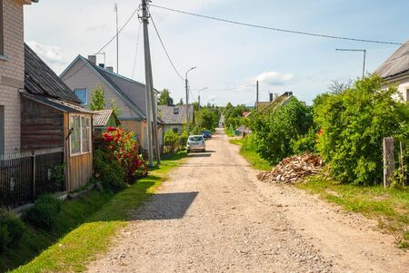 unpaved road: Unpaved road surrounded by rural houses in Siauliai village, Lithuania Stock Photo