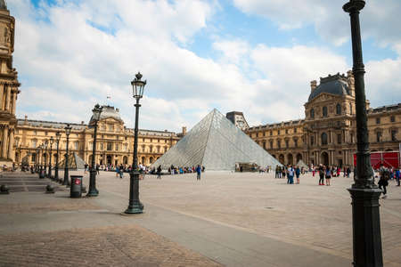 louvre pyramid: PARIS, FRANCE - JUNE 9: Tourists walking aroung Louvre pyramid in Paris, june 2015