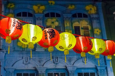 china town: View on bright illuminated garland against of beautifully painted building facade in China town, Singapore