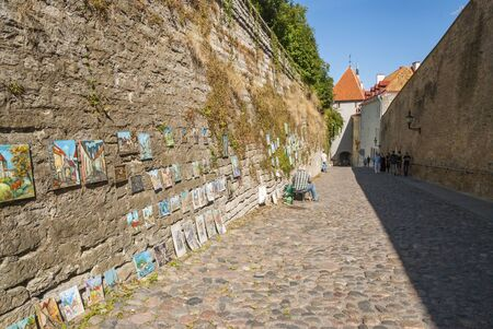 sidewalk sale: TALLINN, ESTONIA - AUGUST 15: Unrecognizable man selling paitings while sitting on sunny street of Tallinn old town. August 2015 Editorial