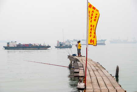 georgetown: GEORGE TOWN, MALAYSIA - OCTOBER 24: Fisherman fishing from a pier in Georgetown on hazy day. October 2015 Editorial