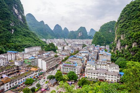 YANGSHUO CHINA - JUNE 12: View over skyline of Yangshuo surrounded with recognizable karst landscape. Karst mountains are the biggest tourist attraction in Guilin region. June 2016