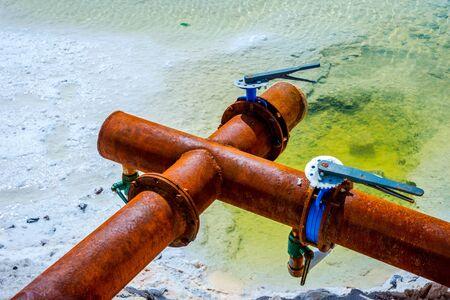 Rusted metal pipes at Chaqia Salt lakes Qinghai China