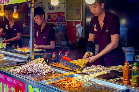 GUILIN CHINA - JUNE 11: People preparing sea food skewers at food corner in Guilin China. June 2016