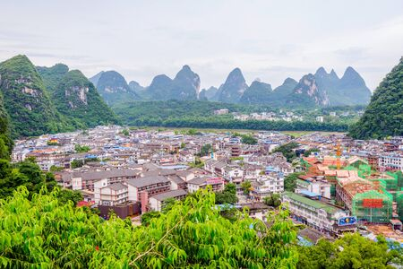 YANGSHUO CHINA - JUNE 12: View over skyline of Yangshuo surrounded with recognizable karst landscape and Li River. Karst mountains are the biggest tourist attraction in Guilin region. June 2016 Editorial