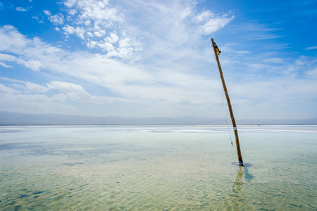 View over Chaqia (Chakayan) salt lake and abandoned electric pillar Qinghai China on sunny day