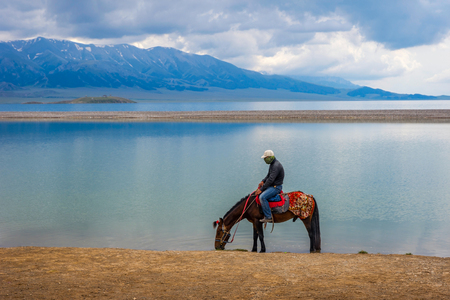 xinjiang: BOLE CHINA - JULY 4: Single horse rider resting by the Sayram lake Xinjiang Uyghur autonomous region. July 2016 Éditoriale