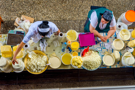 ALMATY, KAZAKHSTAN - JULY 15: Women selling home made dairy products, cheese, butter and cream at Green bazaar, view from above. July 2016