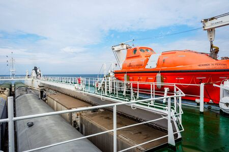 Orange rescue boat on the cargo vessel at the sea