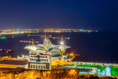 azeri: BAKU, AZERBAIJAN - SEPTEMBER 21: Caspian Waterfront shopping mall under construction at night, Baku. September 2018