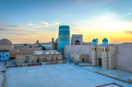 도시 벽과 일몰, 우즈베키스탄에 minaret Khiva 오래 된 마을