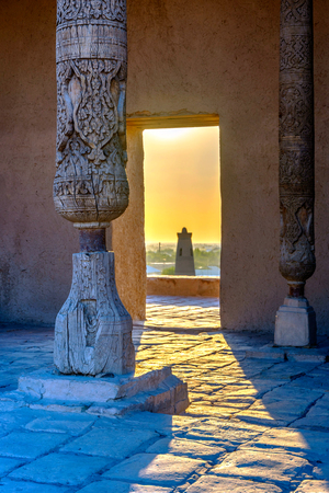 thru: Old wooden pillars, and sun shining thru the door with the view to the minaret of Khiva old town, Uzbekistan Stock Photo