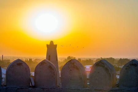 Silhouette of old city wall and minaret in sunset, Khiva, Uzbekistan