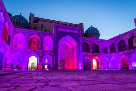 Illuminated colorful atrium of Sher-Dor Madrasah at night, Samarkand Registan, Uzbekistan Stock Photo