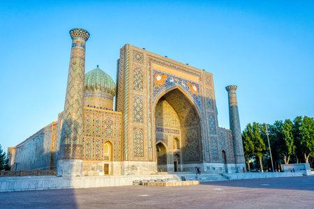 registan: SAMARKAND, UZBEKISTAN - AUGUST 27: Visitors in front of Sher-Dor Madrasah  in Samarkand in afternoon sun. August 2016