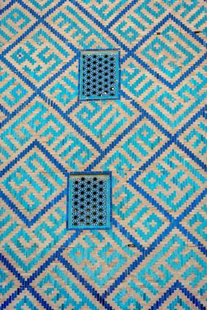 Detail of window on the wall with blue tiles pattern of Samarkand Registan, Uzbekistan