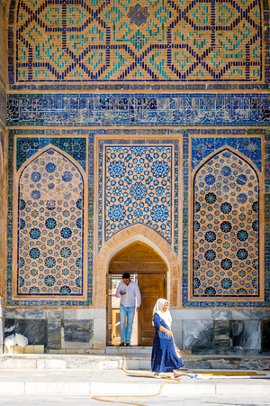 SAMARKAND, UZBEKISTAN - Woman and man in front of colorful wall of blue mosaic in Samarkand, Registan, Uzbekistan. August 2016 Editorial