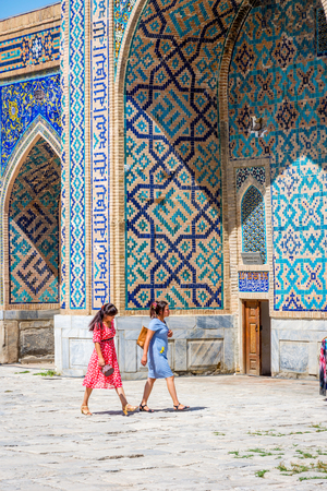 SAMARKAND, UZBEKISTAN - AUGUST 28: Two woman passing the entrance to the souvenir shop in the atrium of Samarkand Registan, Uzbekistan. August 2016