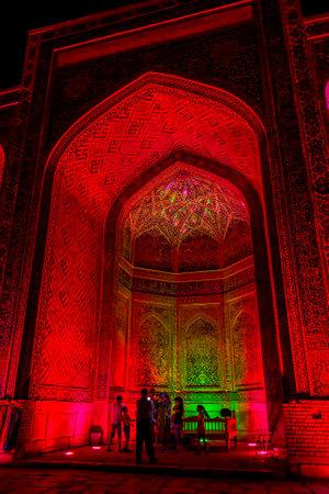 registan: SAMARKAND, UZBEKISTAN - AUGUST 28: People taking photos in atrium of Sher Dor madrasah at night, Registan, Samarkand. August 2016