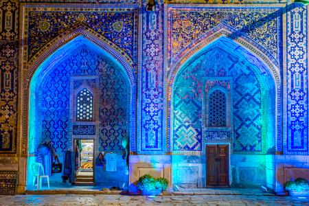 Shop in lit up atrium of Sher Dor madrasah at night, Registan, Samarkand, Uzbekistan