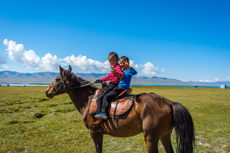 SONG KUL, KYRGYZSTAN - AUGUST 11: Two kids riding and greeting from a horse by Song Kul lake. August 2016