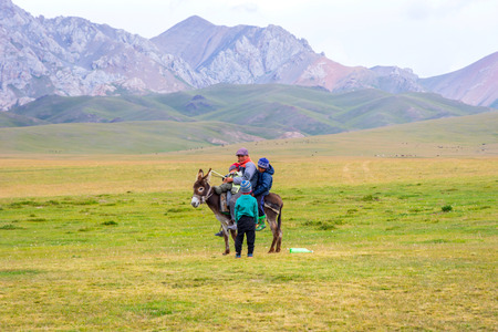 SONG KUL, KYRGYZSTAN - AUGUST 10: Man and three kids climbing up the donkey to go for a ride at Song Kul lake. August 2016 Editorial