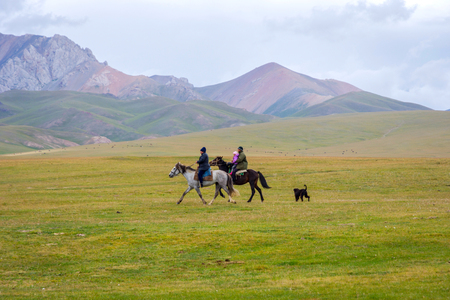 SONG KUL, KYRGYZSTAN - AUGUST 10: Woman and a man with a kid in the lap riding the horses and the dog following them around scenic Song Kul lake. August 2016 Editorial