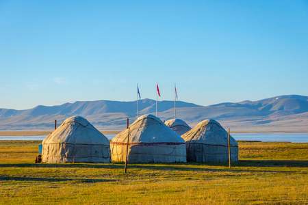 Yurts and flag poles by song kul lake, Kyrgyzstan Stock Photo
