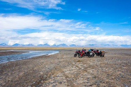 Group of motorbikes next to the river in a scenic valley of Tian Shan mountains, Kyrgyzstan Stock Photo