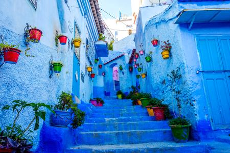 モロッコ、シェフシャウエンのカラフルな花のバケツを持つ青い通り