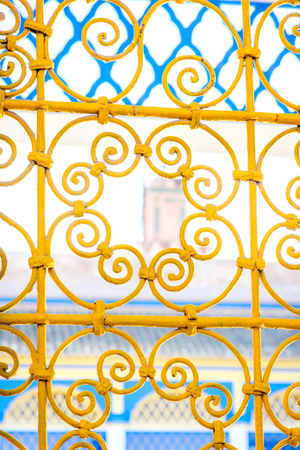 Yellow ornamental lettice against blue building at Bahia palace backyard, Marrakech, Morocco