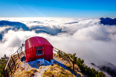 Bivacco Dino bivouac with the sea of clouds under. The Alps, Italy