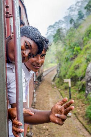IDALGASHINNA, SRI LANKA - FEBRUARY 2: Two local school kids in uniforms hanging out the train. February 2017