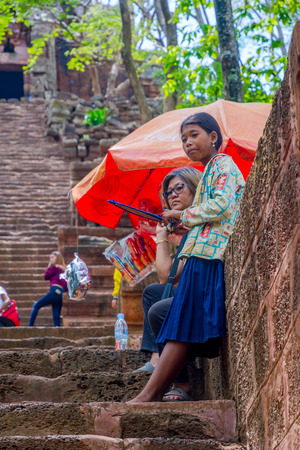 BATTAMBANG, CAMBODIA - APRIL 1: Local girl standing at the staircase of the Wat Banan temple and selling souvenirs. April 2017 Editorial