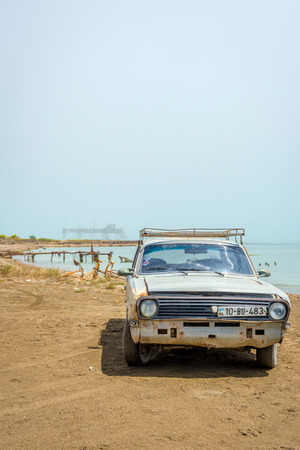 SHURAABAD, AZERBAIJAN - MAY 5: Old soviet Volga car and abandoned oil rig on the shore of Caspian sea, Azerbaijan. May 2017
