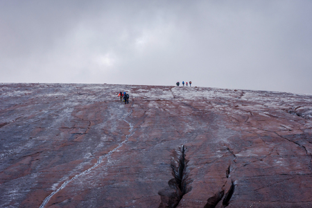 Group of unrecognizable people walking on Kazbegi glacier, Georgia