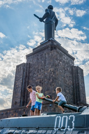 Yerevan, Armenia - August 20 2017: Kids playing on the tank with mother Armenia monument behind, in Victory park in Yerevan Stock fotó - 102857231