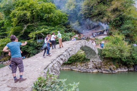 Makhuntseti, Georgia - August 26, 2017: People walking and taking photos on Makhuntseti bridge, a known tourist place in Adjara region Редакционное