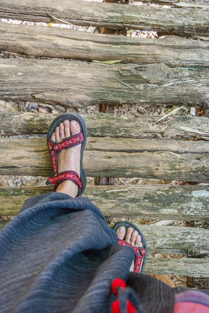 Walking over the wooden bridge in sandals, first person view, travel time